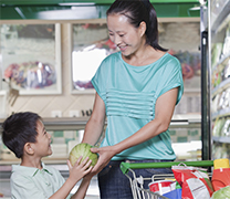 A mother hands her child some produce.